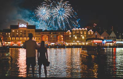 Couple watching fireworks at night across a waterway at Downtown Disney